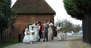 Essex Lady Toastmaster holding Wedding Dress as the Bride leaves the Honeymoon cottage on way to Wedding Ceremony at Gaynes Park, Essex,  photograph courtesy of Divine Photography,